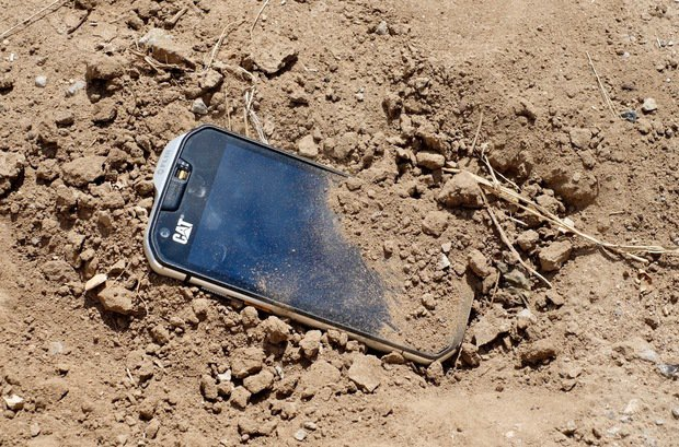cat s60 in a pile of dirt