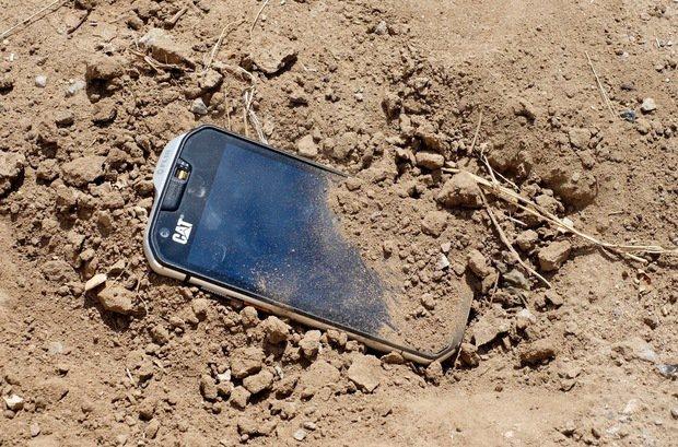 cat s60 in a pile of dirt